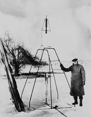 Robert H. Goddard poses in a farmer's field in Auburn, Mass., on the morning of March 16, 1926, with what was to become the first successfully launched liquid-fueled rocket.
