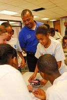 Former NASA astronaut and the first African American to walk in space, Dr. Bernard Harris Jr. watches campers tackle a project.