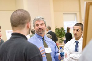 Eric Hahn '80 discusses one of the projects completed by first-year students in the new Great Problems Seminars during a poster session on Dec. 10.