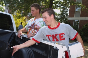 A TKE member, right, helps a fellow student move into a WPI residence hall.