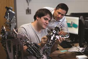 Torres-Jara, right, and Ennio Claretti '13 with a robot hand equipped with sensors that give it the sense of touch.