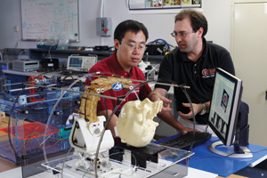 Gregory Fischer, right, and PhD candidate Hao Su with a robot designed to implant electrodes for deep-brain stimulation while inside an MRI scanner.